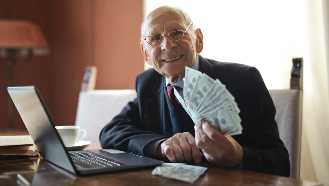 Happy Senior Business Man Holding Money in Haind and Smiling