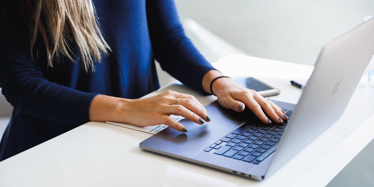 Woman in Blue Long Sleeve Shirt Typing on Laptop